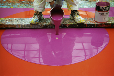 The artist working on Poured Painting: Magenta, Orange, Mage...