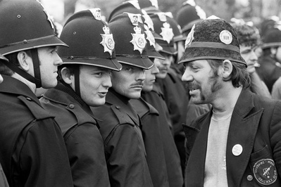 Picket wearing a joke police helmet and police without ident...