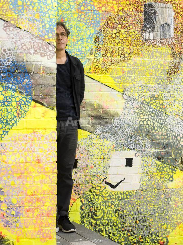 Enlarged version of Jeffrey Dennis in front of his public artwork 'The Luton Host', 2017