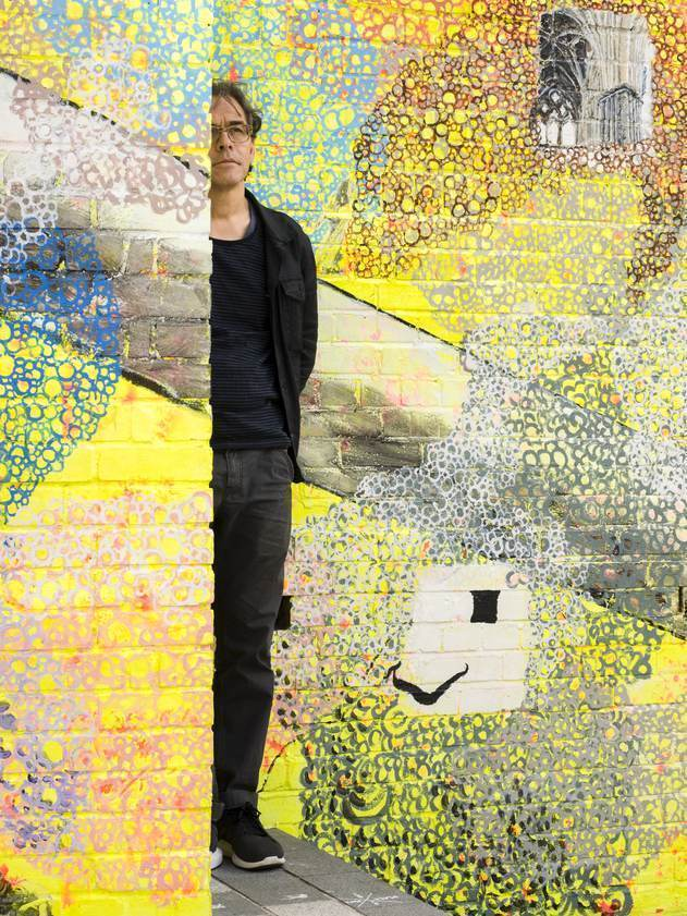Jeffrey Dennis in front of his public artwork 'The Luton Host', 2017