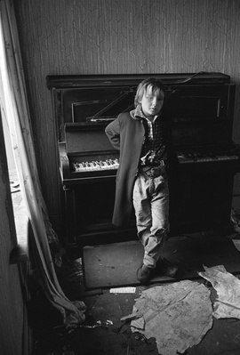 Child leaning on a piano in a derelict house, Byker, 1971