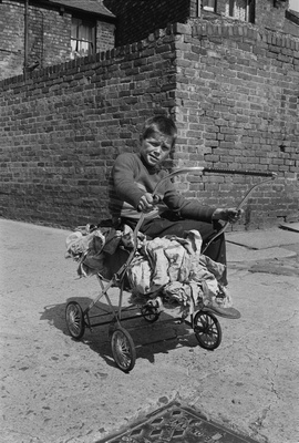 Boy on a pram with rags, Byker, 1974