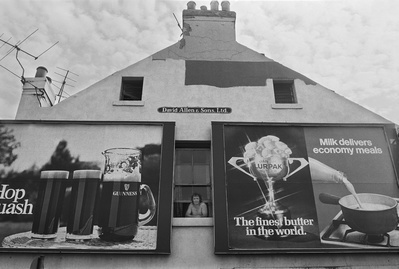 Man in a window flanked by beer and buttter adverts, Byker, ...