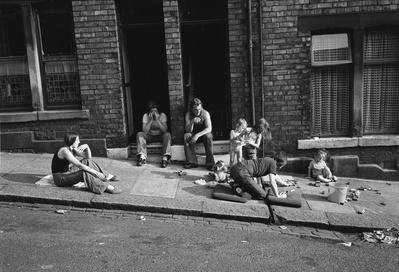 Young families relaxing on the pavement outside their front ...